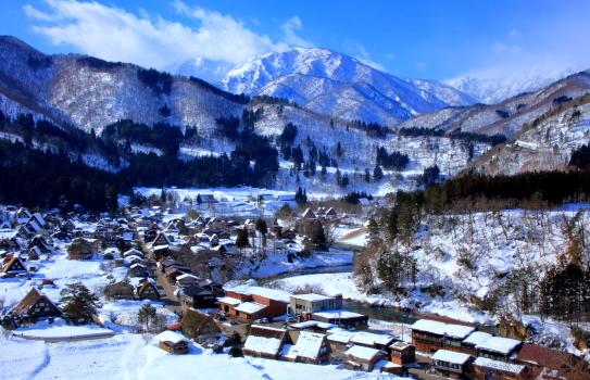 白山の山々を背後に雪の白川郷