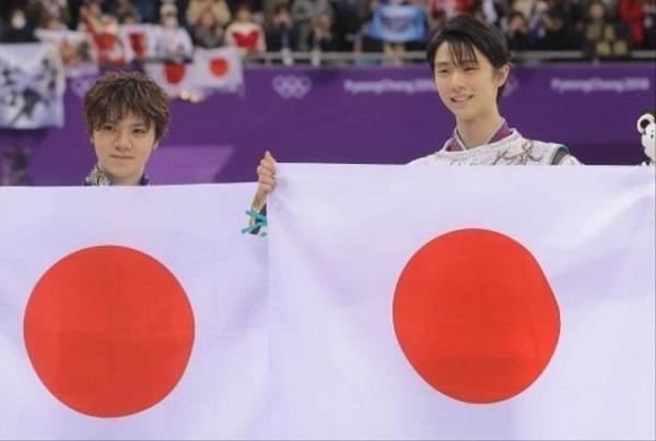 フィギュアスケート男子で金メダルを獲得し、日の丸を手に笑顔の羽生結弦(右)と銀メダルの宇野昌磨=江陵(共同)