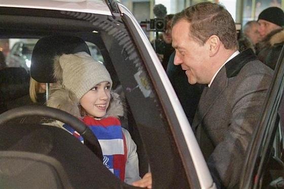 ロシア政府から贈られたドイツ車BMWの新車に乗り込むアリーナ・ザギトワ選手。右はドミトリー・メドベージェフ首相=2月28日、モスクワ(タス=共同)