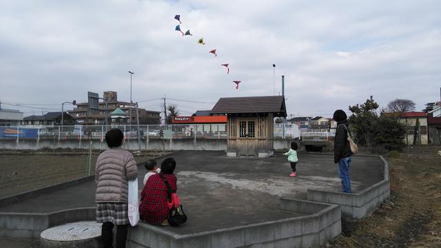 凧を揚げる子供、見てるほかの家族